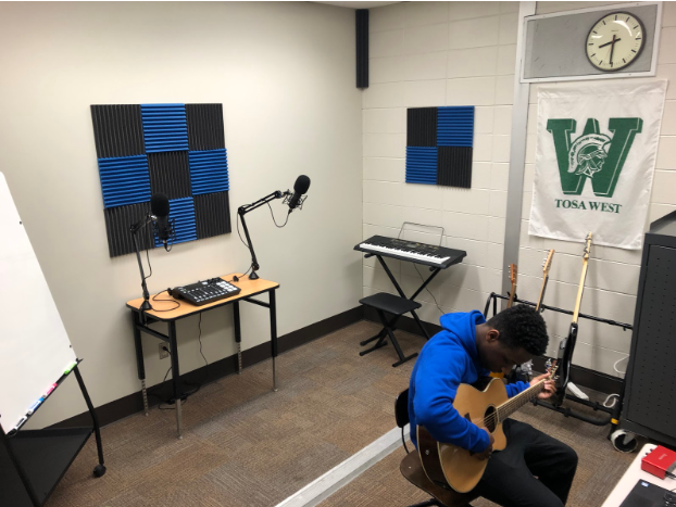 Wauwatosa West student is seen playing the guitar in the new podcast studio in West's library.