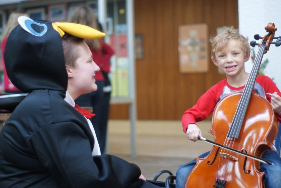 Wauwatosa West Orchestra Sophomore student Keeler Hick teaches a child how to play a cello at Wauwatosa West's 21st annual Kinderkonzert on December 7th.