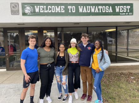 Walkout organizers pose in front of the Wauwatosa West sign.