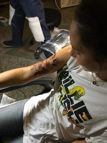 West Senior Isabella Jacobson receives a tattoo on her arm at a tattoo parlor.