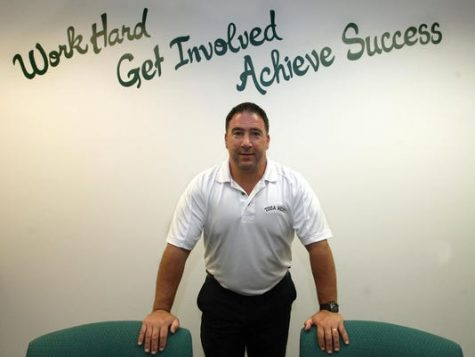 West Principal Frank Calarco stands in front of the inscription on the wall of his office after being first appointed as Principal. Calarcos friend painted the inscription in his office to stress this message to students.
