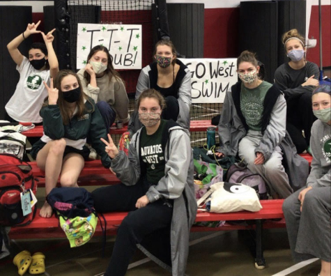 Wauwatosa West students on the Varsity Girls Swim Team sit together before competing at Sectionals.