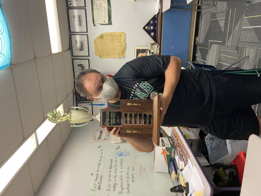 Mr.+Mateske+poses+with+the+homecoming+trophy+that+has+been+proudly+displayed+in+his+room+for+the+last+three+years+in++a+row.+