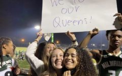 Jami Timmons and Shannon Damuth stand in front of a sign reading We love our queens during the Homecoming Football Game on October 1st.