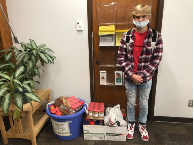 """Evan standing with the peanut butter that was collected for the Tosa Cares Pantry. """"It was more than I expected."""" he said."""